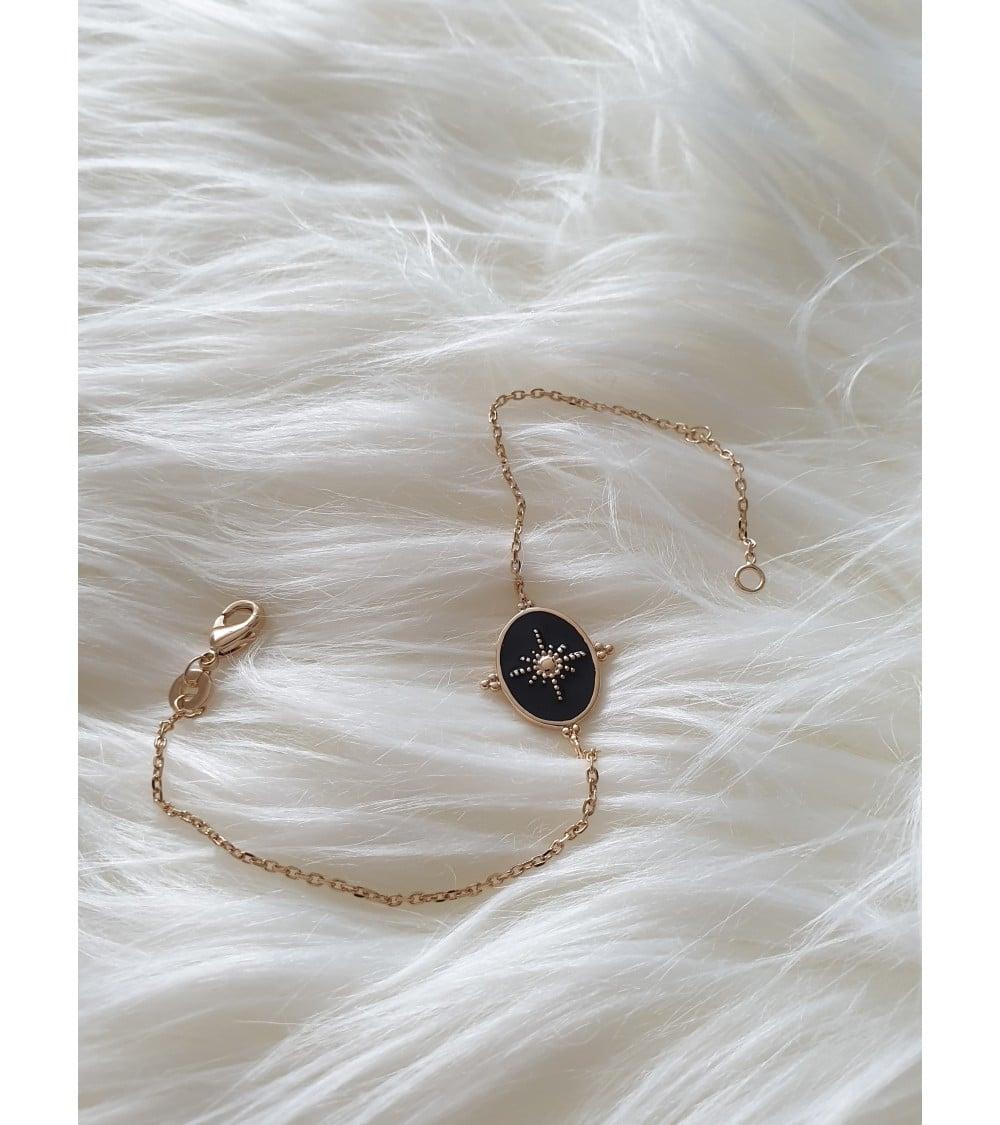 Bracelet en plaqué or avec un ovale réversible, l'un en émail noir et l'autre en plaqué or (longueur 18 cm réglable à 16 cm)