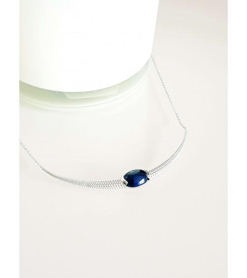 Collier en argent 925/1000 rhodié en arc de cercle à picots avec en son centre un oxyde de zirconium teinté bleu saphir